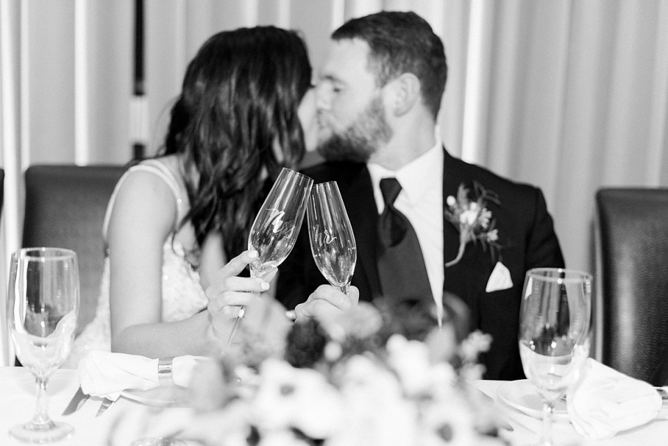 Arielle Peters Photography | Bride and groom kissing and clinking classes at wedding reception.