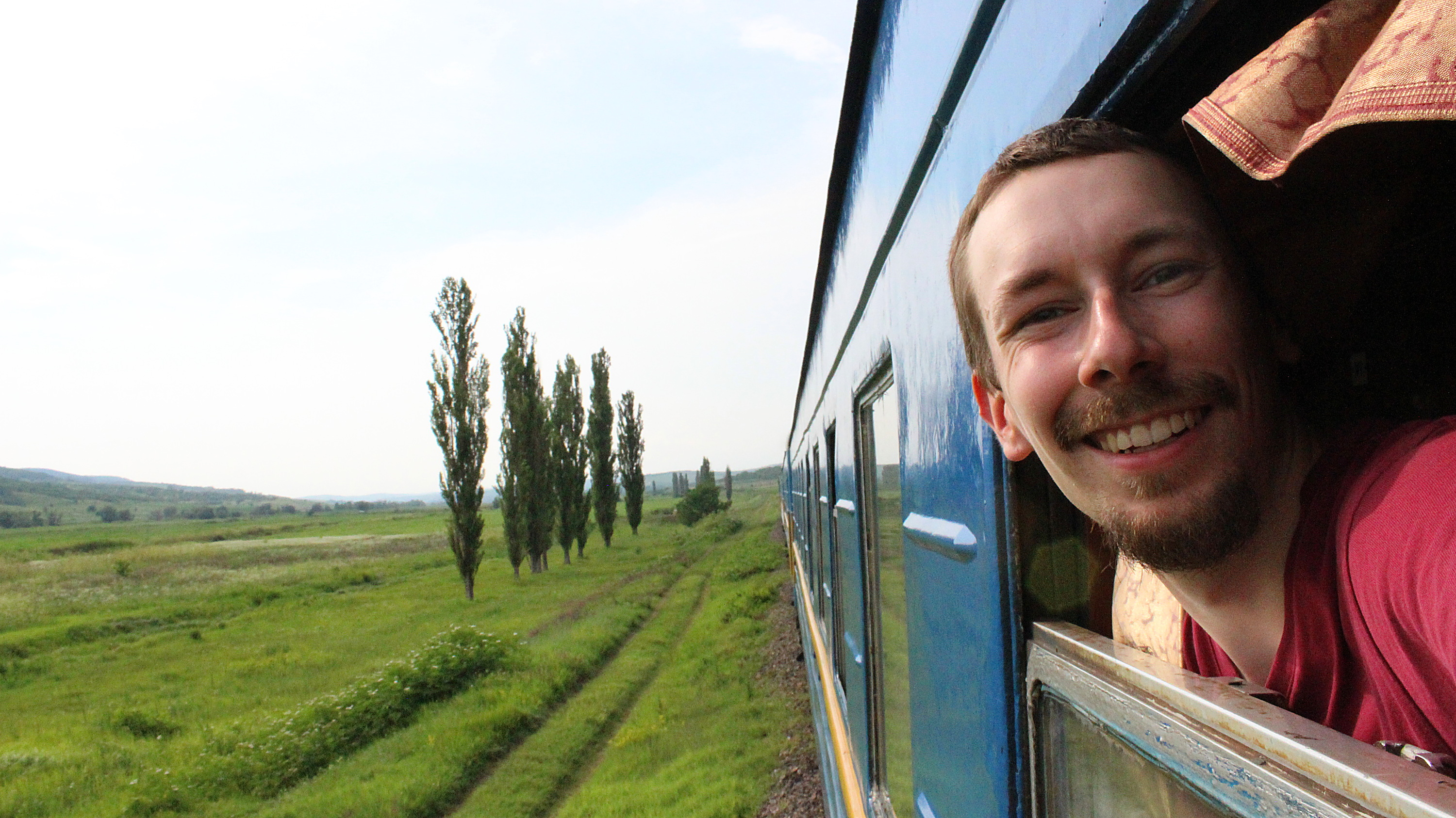 How to waste time during long train journeys? A tourist taking a selfie peeking from an open train window.