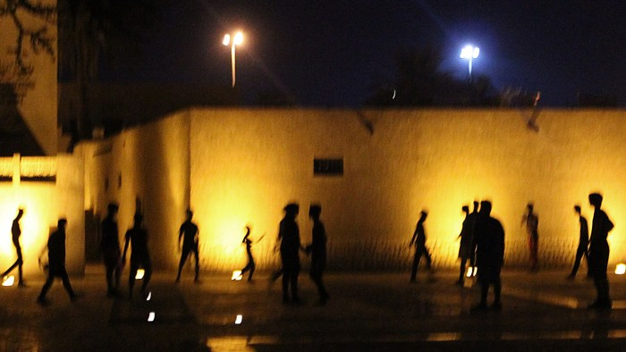 Silhouettes of children playing football at night.