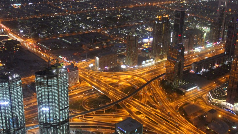 A view of Dubai from Burj Khalifa observation deck at night with lighted highways.
