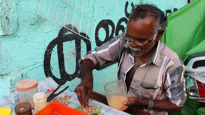 Street vendor making chewable tobacco paan from different ingredients including sprinkles in India.