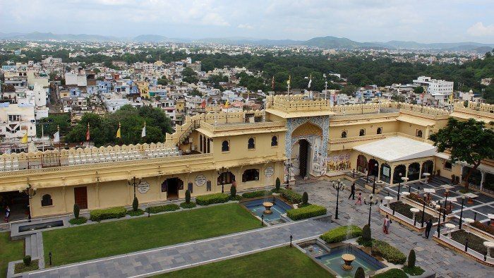 The courtyard of the City Palace of Udaipur from above with a high yellow wall between the yard and the city.