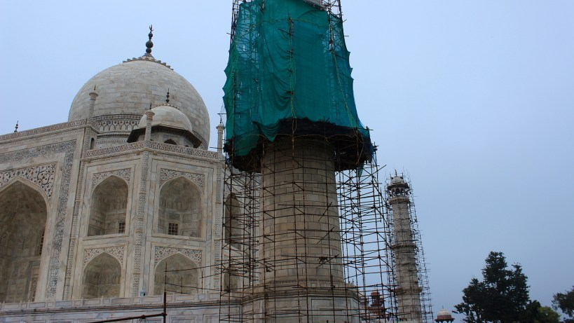 Partly covered minaret tower in front of Taj Mahal under renovation.
