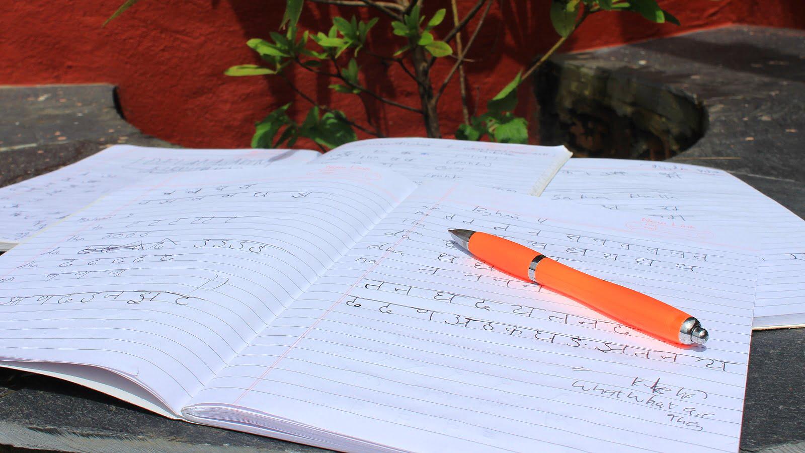 Writing the Nepali language basics. on a notebook.
