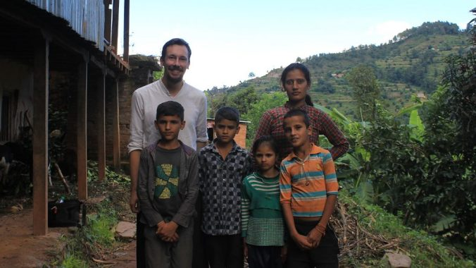 A Western tourist and Nepalese children posing for camera.