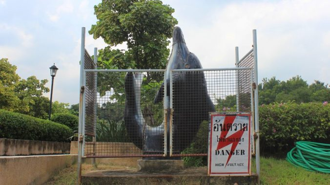 "A fenced dolphin statue with a ""DANGER HIGH VOLTAGE"" sign on the metal fence in a park in Silom, Bangkok."