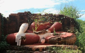A broken Buddha statue with a missing head and a small head in front of it outside in Bagan, Myanmar.