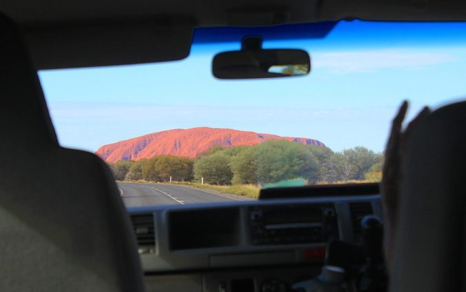 Uluru from far away inside a car.