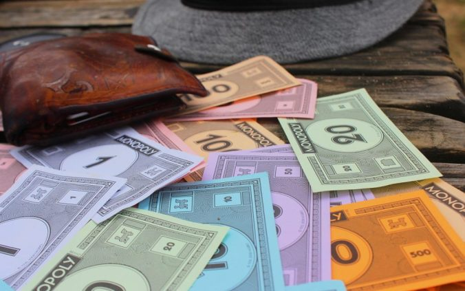 Monopoly money, a wallet and a hat on a dock in Fiji. Best long-term travel tips.