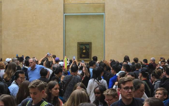 Crowds surround Mona Lisa in Louvre, Paris.