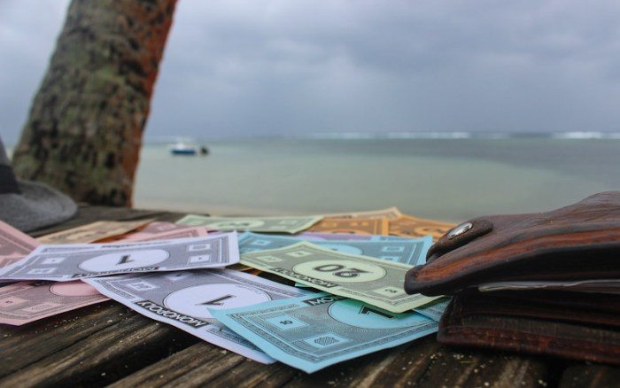 Monopoly money on a beach in Fiji. One Year Travel Budget for a RTW trip.