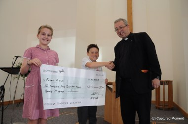 All Saints Junior School pupils Phillippa and Tobias present a cheque to Rev Mark Hayton. Picture by Captured Moment
