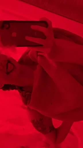 Emma posing as a scarecrow in a red lit bathroom during a Halloween Party in 2019