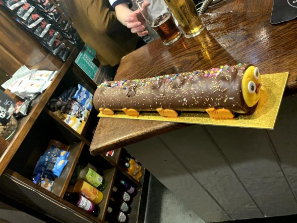 a caterpillar cake on the bar of a haunted pub