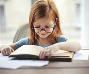 Girl in blue shirt reading book