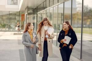 three smiling ladies walking holding books