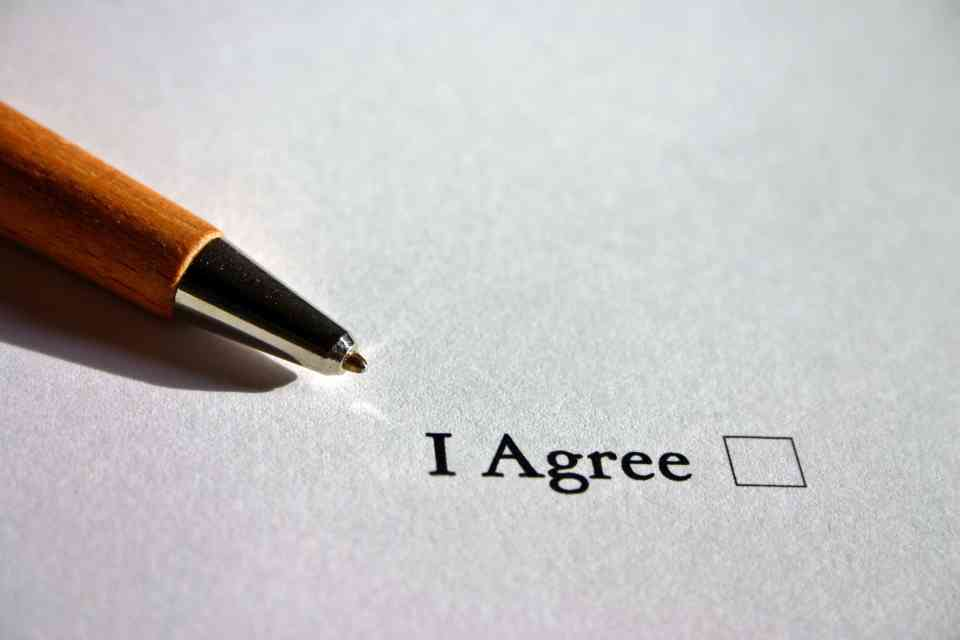 """A pen beside the checkbox with the words """"I Agree""""."""