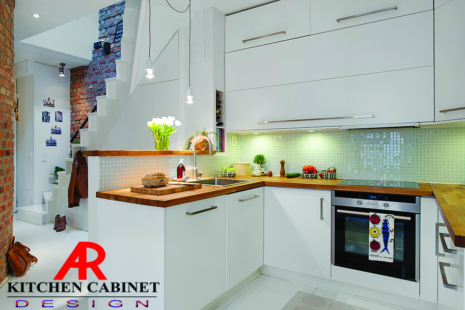 A well lighted modular kitchen. Plants and a chopping board sit on the kitchen counter beside the sink.