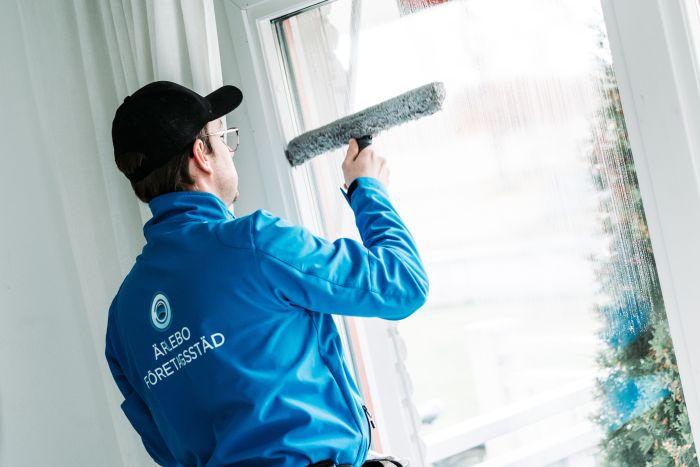 Fönsterputsare från städfirma med blå jacka har ryggen vänd mot kameran rengör ett fönster från insidan