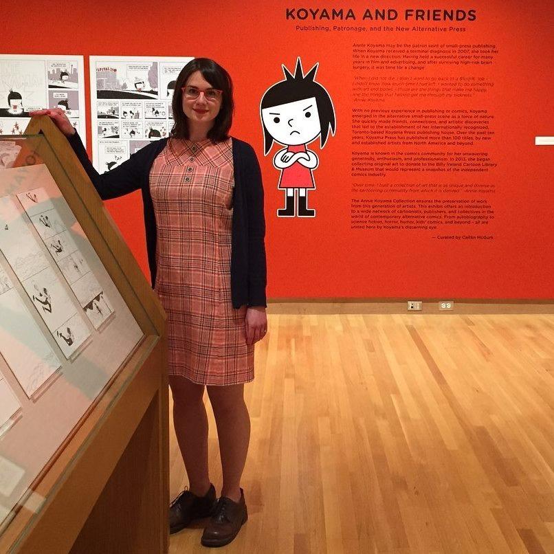 "Photo of Caitlin McGurk standing next to case in exhibit ""Koyama and Friends."""