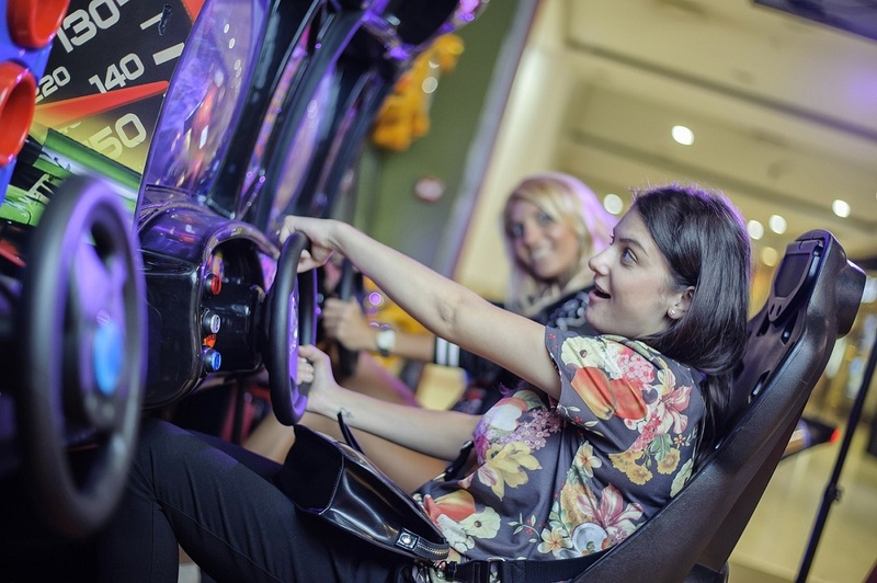 A woman plays a driving arcade machine (via Pixabay)