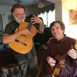 Arnie Gamble and Byron Tomingas playing guitar and ukulele.