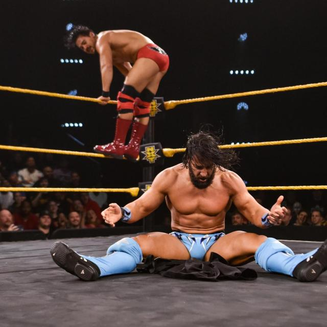 Tony Nese staring at the stripper pants he just powerbombed, with Angel Garza in the background