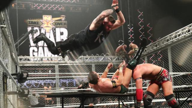 Kevin Owens splashes Kyle O'Reilly through a table to get him to let go of Dominik Dijakovic. Adam COle and Tommaso Ciamp on top of the cage in the background