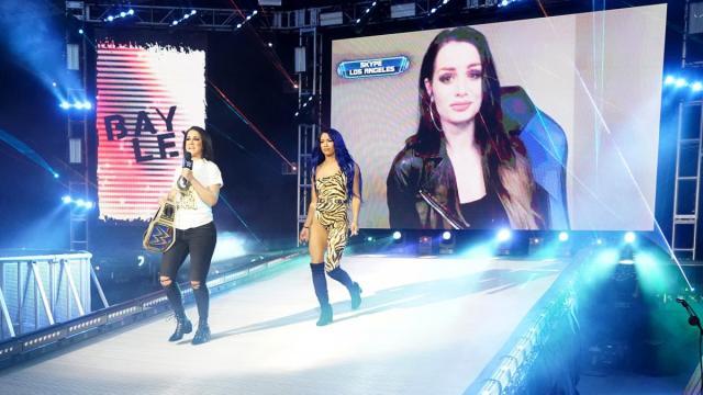 Bayley and Sasha Banks walk down the ramp with Paige on the big screen