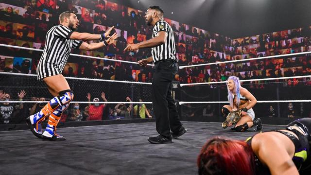 Johnny Gargano argues with the ref while Candice LeRae prepares to hit Io Shirai with the title belt