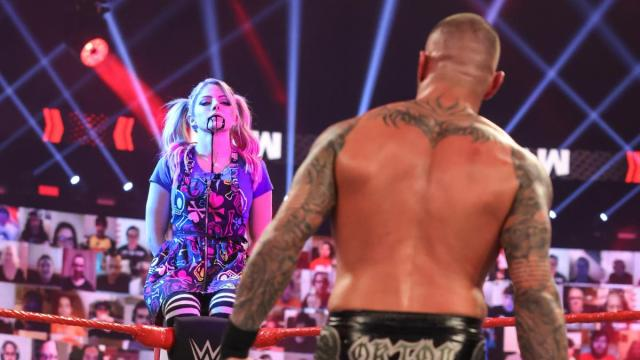 Alexa Bliss, with black goop dribbling out of her mouth, observes Randy Orton from a turnbuckle