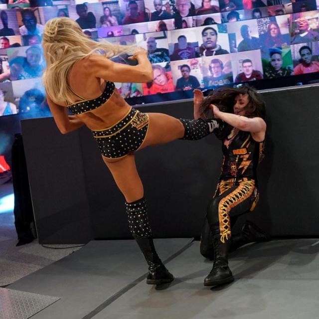 Charlotte Flair kicks Nikki Cross' head into the barricade.