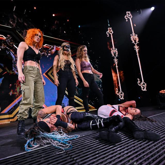 Gigi Dolan, Mandy Rose, and Jacy Jayne stand over Kayden Carter and Kacy Catanzaro