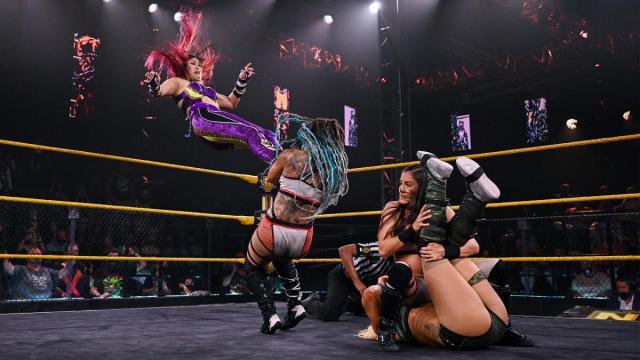 Io Shirai missile dropkicks Kayden Carter onto Kacy Catanzaro to stop her pinning Zoey Stark
