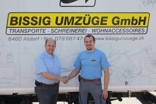Firmenübergabe des bisherigen Inhabers Heinz Bissig an Ambros Arnold vor Umzugslastwagen