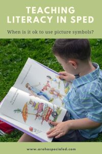 Teaching Literacy in SpEd. When is it ok to use picture symbols? A boy sitting on grass looking at a picture book. The book is open and shows a picture of a Mum and some children playing outside on one page and an overloaded trolley of toys on the other.