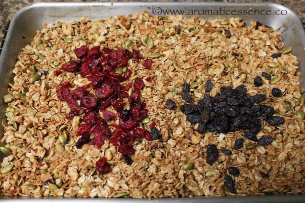 Remove the granola from the oven and add the raisins and cranberries