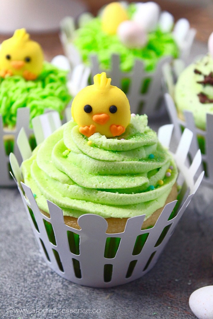 close up of eggless Easter cupcakes with green vanilla buttercream frosting, green sugar dusting, and chick topper