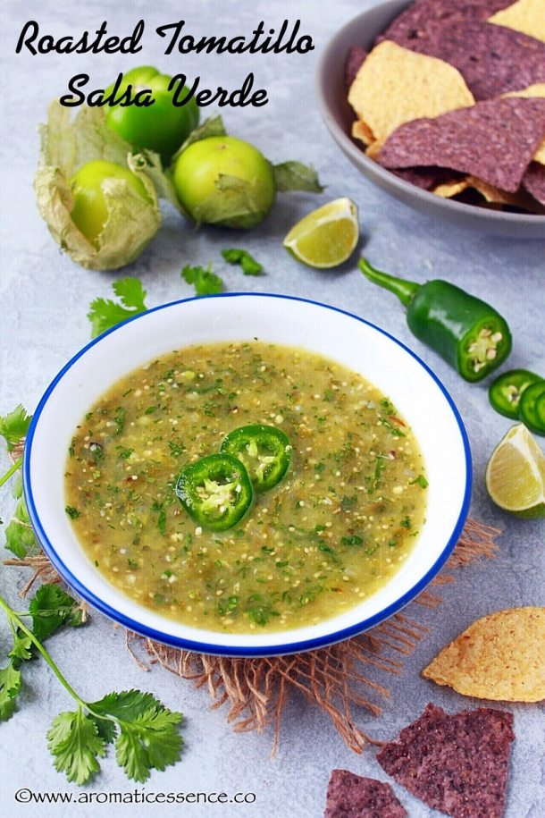 Salsa verde in a white bowl, garnished with serrano pepper slices.