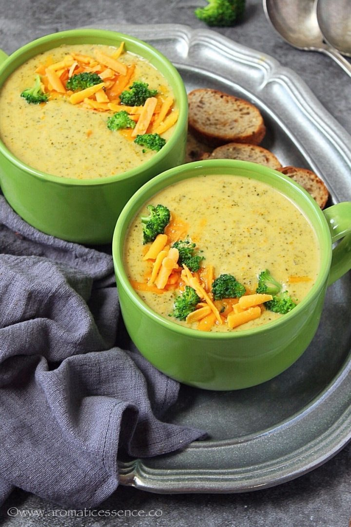 Instant Pot broccoli cheese soup topped with steamed broccoli and shredded cheddar cheese.
