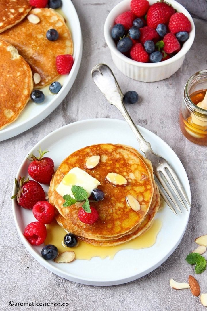 Three pancakes stacked in a white rimmed plate topped with butter, syrup, and berries