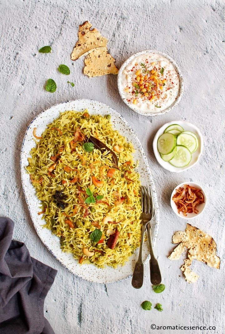 Mint rice served in a deshaped oval platter served along with sliced English cucumber, boondi raita, and papad