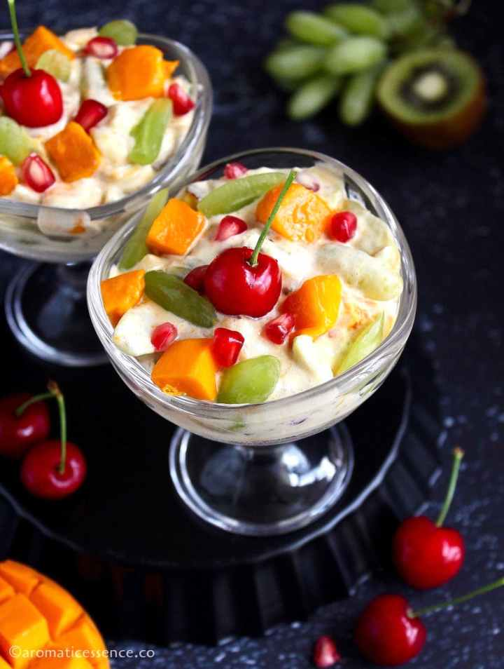 45 degree angle shot of creamy fruit salad in two dessert bowls placed on an inverted black fluted pan