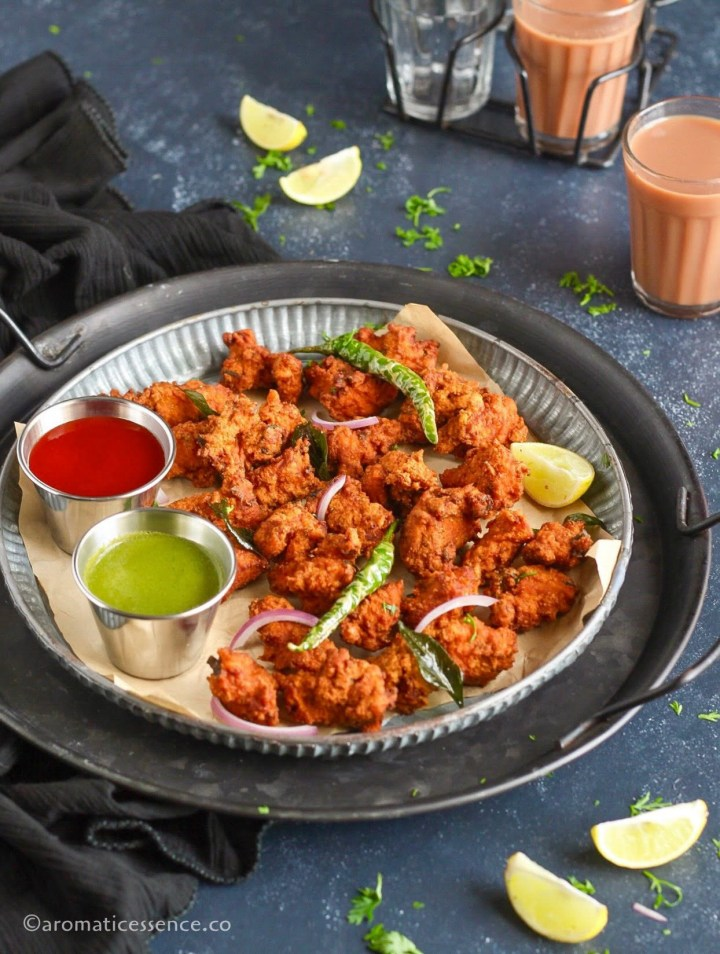 Chicken pakodi garnished with fried green chilies and curry leaves, served in a galvanized rimmed plate
