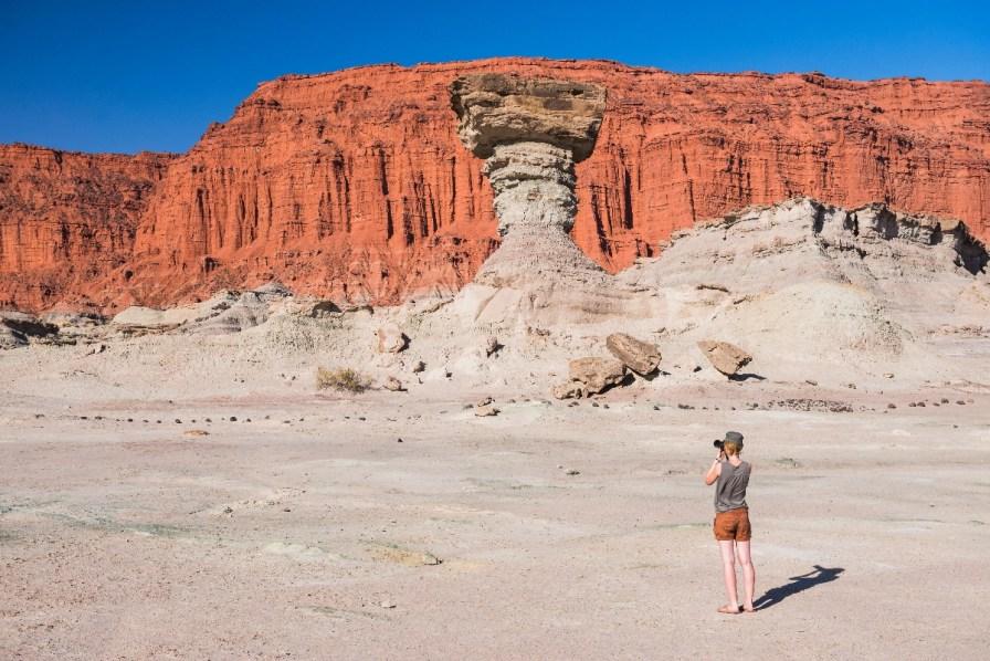 Tourist taking a photo of 'The Mushroom' rock formation by Los Coloradas red rock wall, Valley of the Moon (Valle de la Luna), Ischigualasto Provincial Park, San Juan Province, North Argentina
