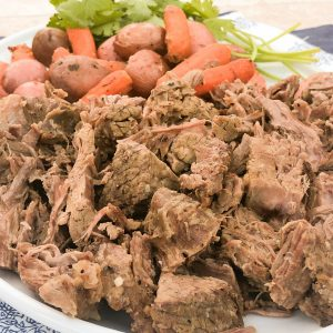 shredded pot roast on white platter with carrots and potatoes   3 Packet Pot Roast Recipe