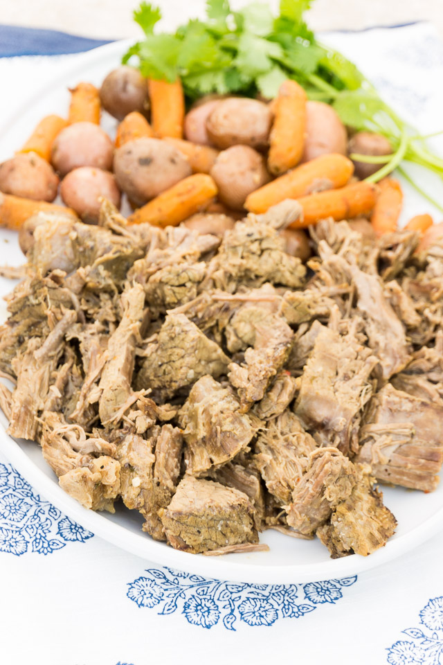 shredded pot roast on white platter with carrots and potatoes | 3 Packet Pot Roast Recipe