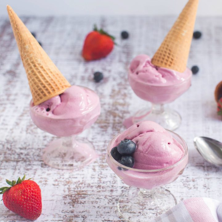 scoops of pink frozen dessert in glass cups with sugar cones on top