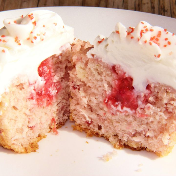 fresh strawberry cupcake topped with almond buttercream frosting, cut in half