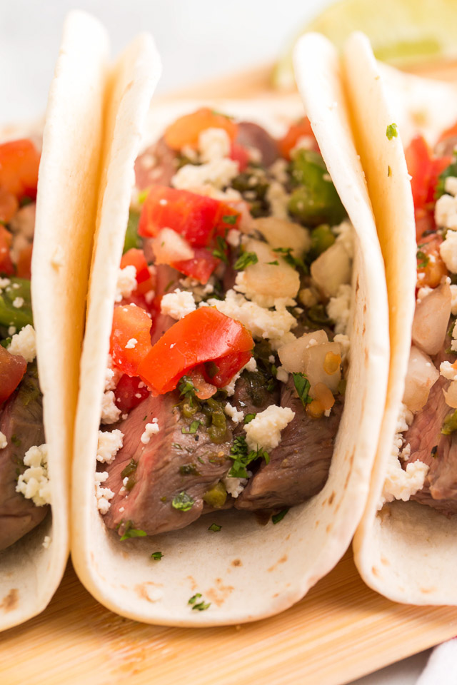 close up image of steak taco with diced tomatoes, crumbly Mexican cheese and seasonings